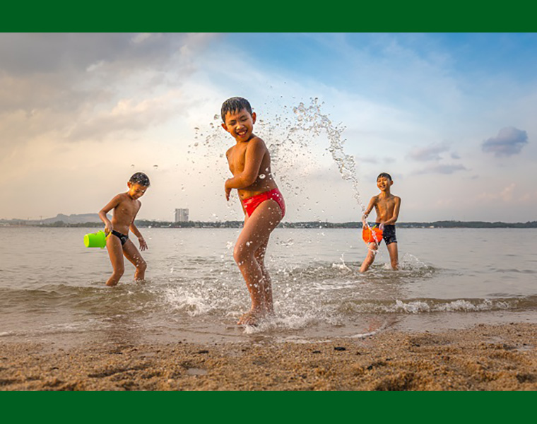 Children playing by the beach splashing water